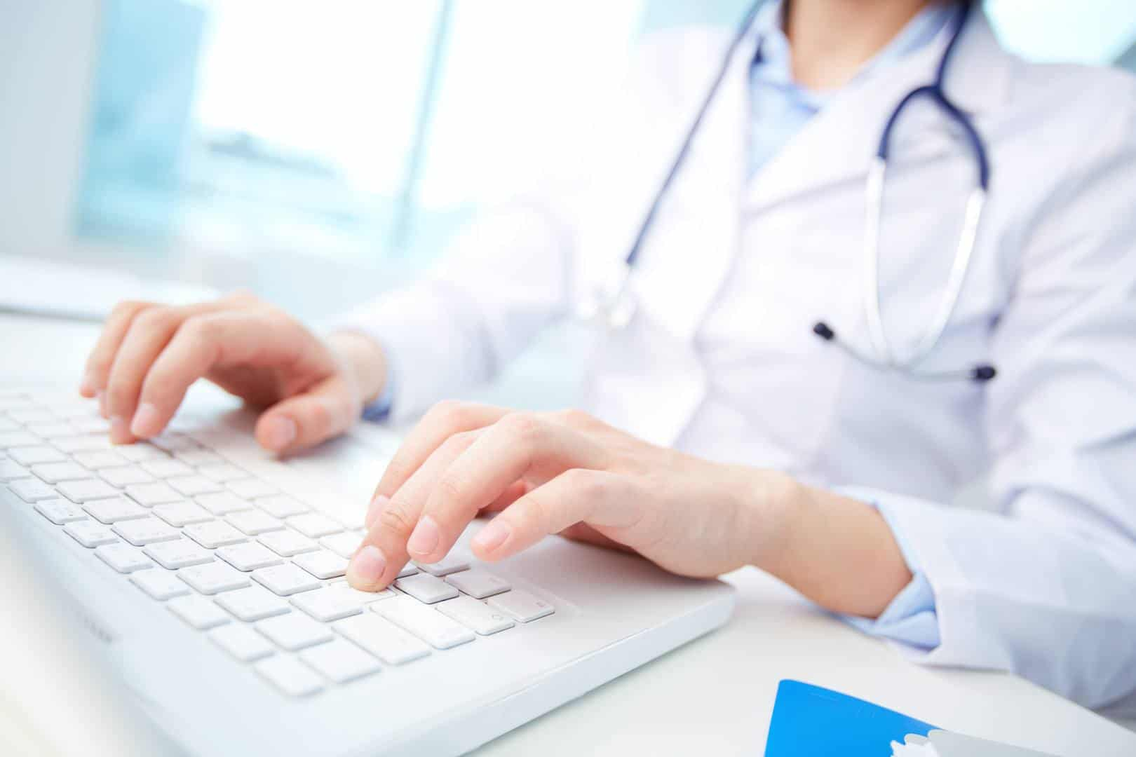 medical person wearing stethoscope typing on a keyboard