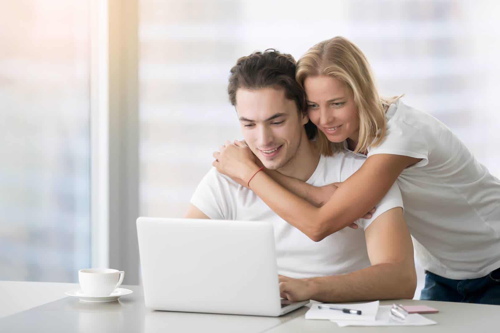 young couple looking for homes online