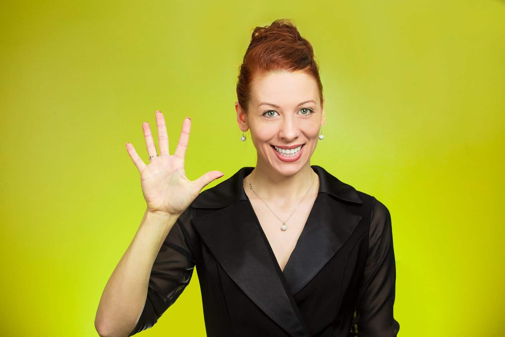 Closeup portrait, happy, smiling young woman making five times sign gesture with hand fingers, isolated green background. Positive human emotion facial expression feelings, attitude, symbol, reaction